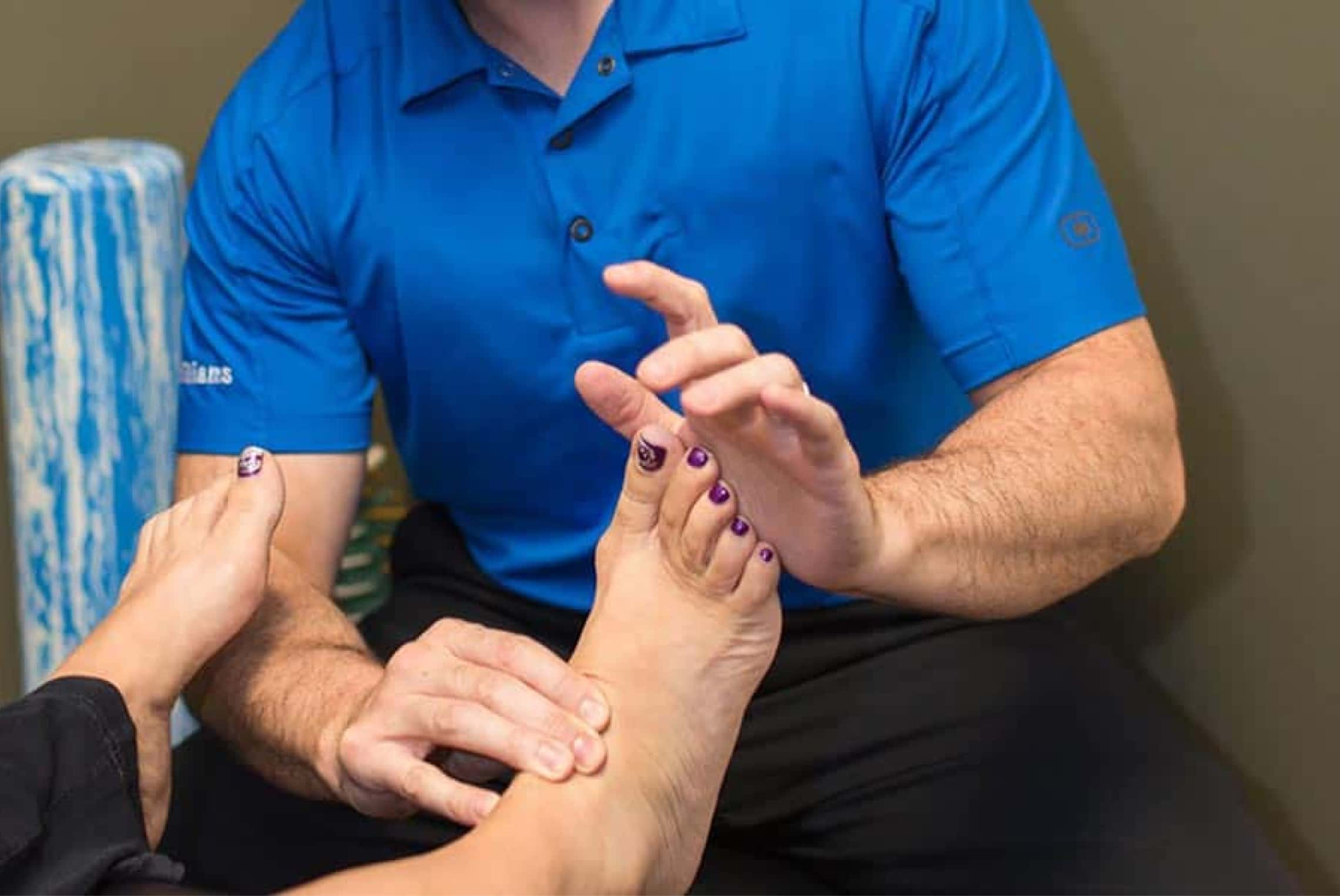 Chiropractor pushing against woman's toes while holding ankle