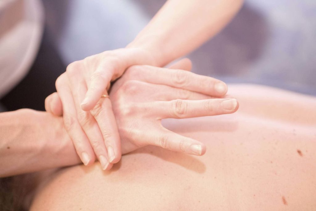 hands on the upper back of massage patient